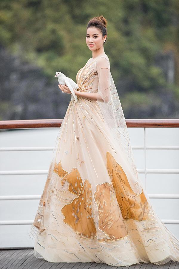 Phạm Hương toả sáng như một nữ thần với thiết kế váy dạ hội được thêu kết tỉ mỉ hình ảnh những tia sáng tràn đầy năng lượng của mặt trời. Đồng thời phần tùng váy cũng được tạo điểm nhấn bằng hình ảnh kỳ quan thiên nhiên.