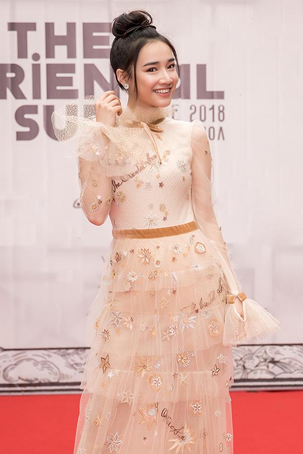 Xuất hiện trong show diễn thời trang được tổ chức tại Vịnh Hạ Long, diễn viên Nhã Phương giúp mình tôn nét khả ái với mẫu váy mới nhất của Lê Thanh Hoà. Váy màu nude thêu hoạ tiết mặt trời, trăng, sao tinh tế được trang trí thêm phần tay loe và cổ xếp bèo nhún nhẹ nhàng.