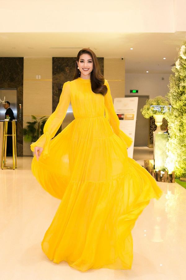 Hoa hậu Hoàn vũ Việt Nam xách váy tạo dáng trước ống kính. Gương mặt cô trông rất rạng rỡ.
