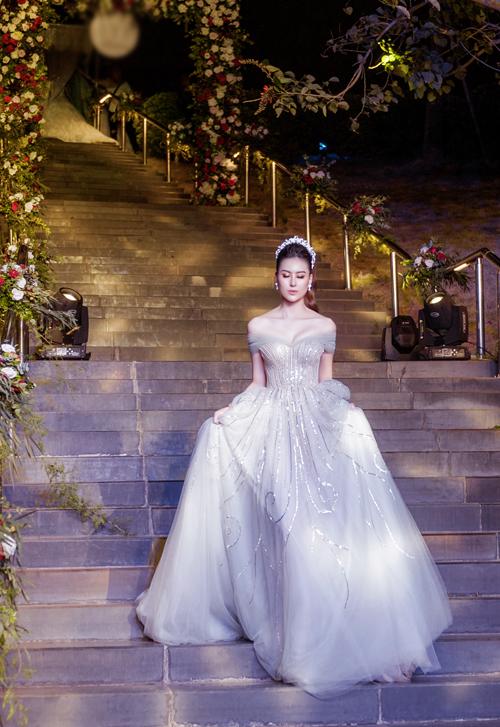 Trong một mẫu váy khác, Hà Lade lại khoe được vẻ đẹp dịu dàng và gợi cảm của mình. Chiếc váy thêu kim tuyến trễ vai gợi sự liên tưởng đến trang phục của nàng công chúa Bella trong truyện cổ tích.