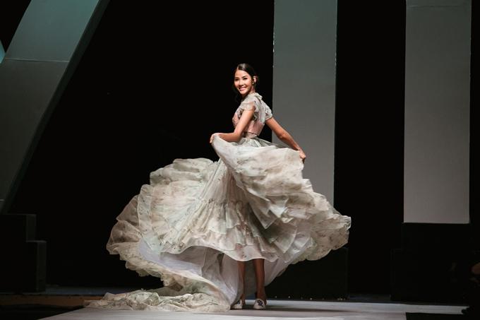 Xuất hiện trên đường băng thay vì phong cách catwalk theo chuẩn runway quốc tế, Hoàng Thùy liên tục thể hiện động tác tay để bung xòe mẫu váy dài 4 mét.