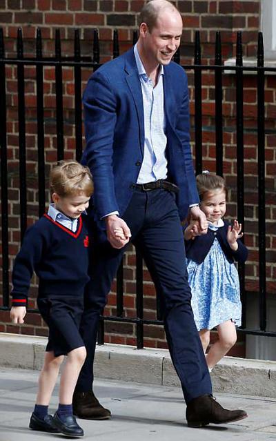 Hoàng tử William nắm tay hai con vào bệnh viện thăm em bé mới sinh. Ảnh: Reuters