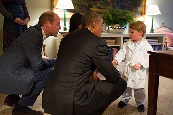 Hoàng tử George mặc đồ ngủ bắt tay và trò chuyện với vợ chồng cựu tổng thống Mỹ Barack Obama hồi tháng 4/2016. Ảnh: AFP