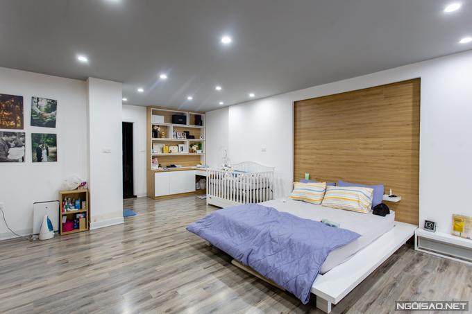 Khác với những không gian còn lại của ngôi nhà, phòng ngủ chính được lát sàn gỗ sáng màu và hàng chục chiếc đèn âm trần. Điểm nhấn nằm ở mảng tường bằng gỗ nằm ở