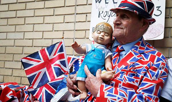 Ông Hutt mặc đồ toàn in hình quốc kỳ Anh, bế theo búp bê hình một bé trai.Ảnh: Express
