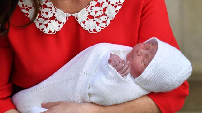 Giống như hai anh chị của mình, cậu bé được mẹ bế trên tay khi ra mắt công chúng. Hoàng tử nhí được quấn một lớp chăn len trắng và đội mũ cùng màu.