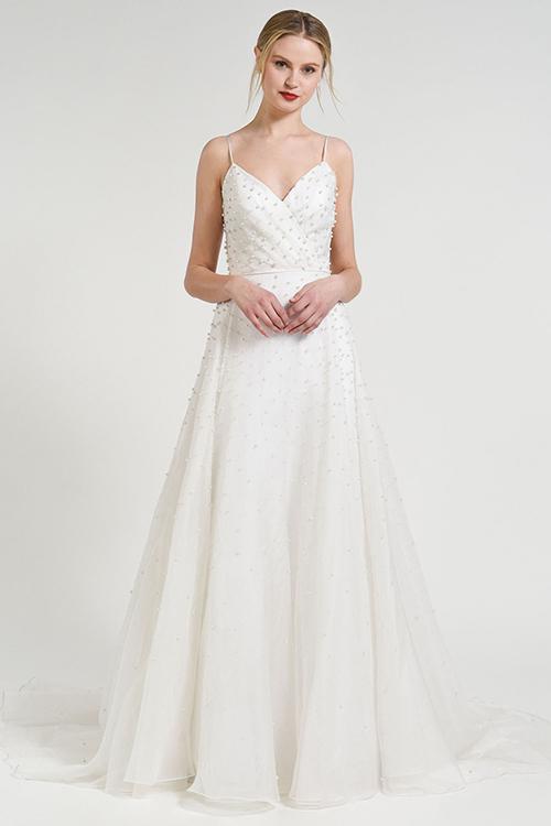 Mẫu váy từ thương hiệu Anny Lin có gắn ngọc trai trên phần áo choàng ngoài của cô dâu.