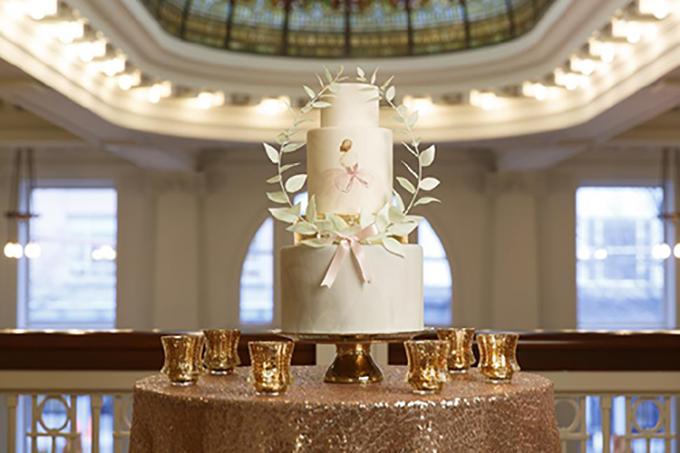 Bánh cưới mang màu trắng chủ đạo được tô điểm bởi chiếc vòng nguyệt quế và dải ruy băng hồng.