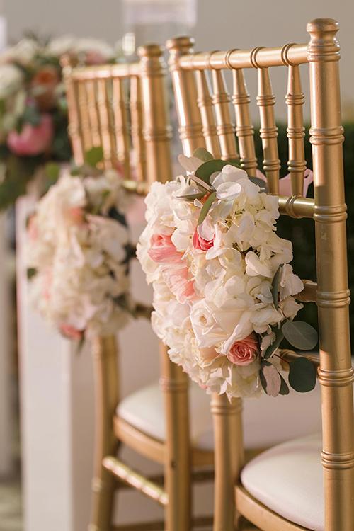 Những chiếc ghế được trang trí bằng hoa hồng và hồng trắng.