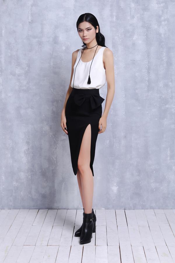 Chân váy bút chì trở nên mới lạ hơn nhờ đường xẻ tôn vẻ đẹp sexy và điểm nhấn không thể thiếu là chiếc nơ xinh xắn để tạo nên sự hoà hợp với tổng thể.