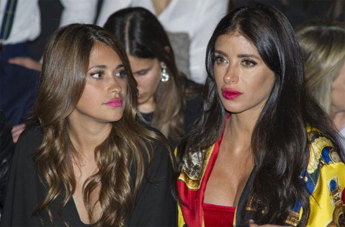 Hai cô bạn thân ngồi cạnh nhau khi xem show thời trang.