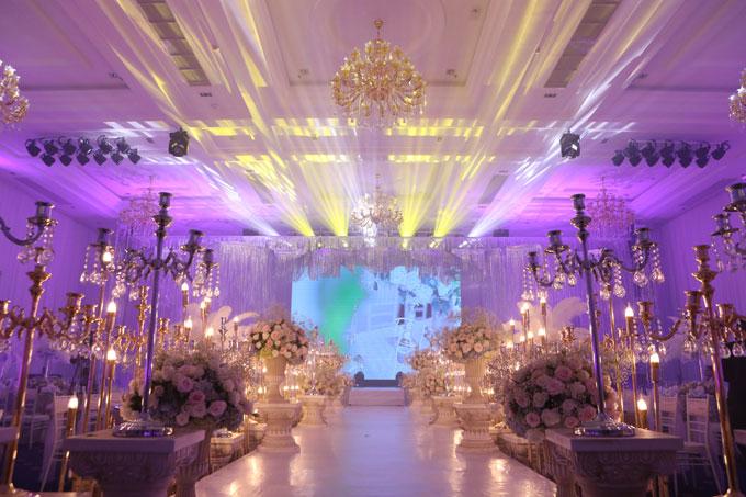 Không gian của sự kiện được thiết kế, trang trí như một bữa tiệc cưới sang trọng, đẳng cấp với hoa và đèn nến ngập tràn. Dọc hai bên đường đi lên sân khấu là những chậu hoa màu hồng phấn và cây đèn nến tạo không gian lãng mạn .