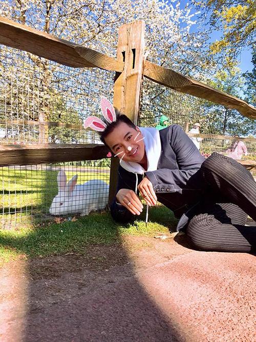 Đàm Vĩnh Hưng ngồi sát xuống đất để chụp ảnh cùng chú thỏ đáng yêu trong vườn thú.
