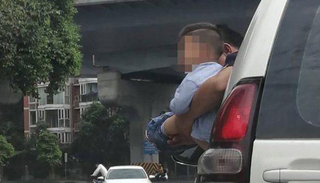 Bất chấp nguy hiểm, bé trai bị bế hẳn ra ngoài cửa sổô tô để cho đi tè.