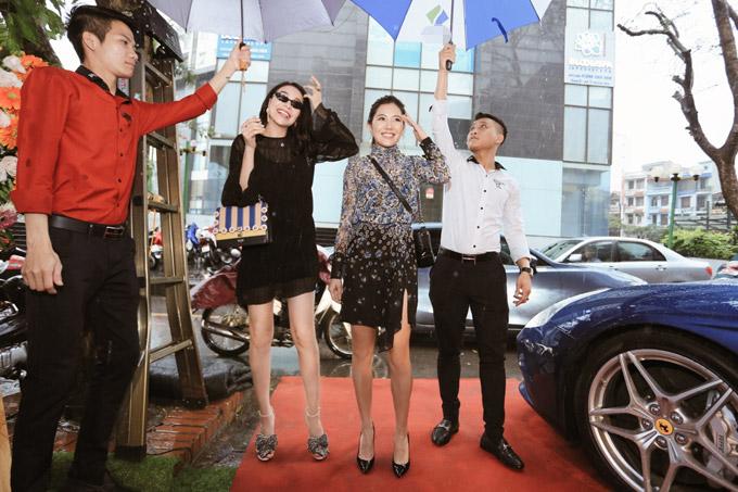 Trà Ngọc Hằng và Milan Phạm cũng xuất hiện tại event sáng qua đúng lúc trời đổ mưa lớn. Cả hai được các nhân viên cầm ô che chắn để không bị ướt. Trà Ngọc Hằng diện váy đen điệu đà và xách túi Fendi gần 4.000 USD cùng giày hiệu 1.500 USD.