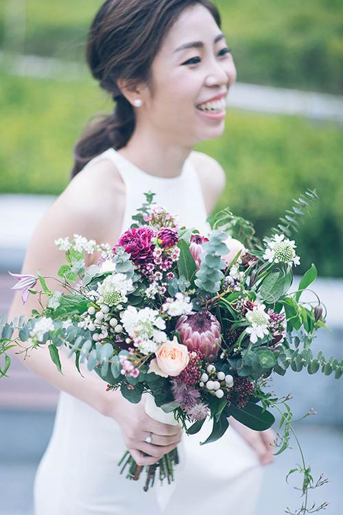 Cô dâu rạng rỡ bên bó hoa điểm xuyết sắc đỏ tía.