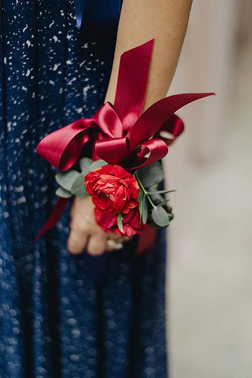 Bó hoa cầm tay mang chút sắc đỏ của cô dâu và bộ cánh xanh đen của chú rể đem đến sự đối lập về màu sắc vui mắt và thú vị.