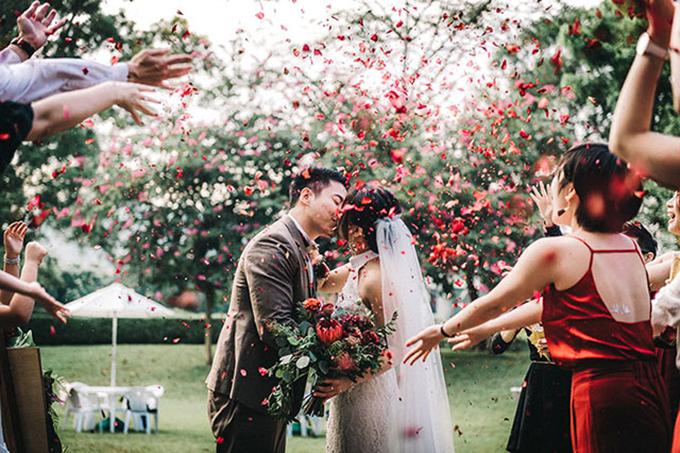 Khách mời tung cánh hồng đỏ thẫm để mừng hạnh phúc của cặp mới cưới.