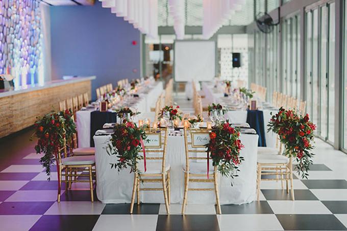 Bàn tiệc được tô điểm bởi những khóm hoa đỏ và khăn trải bàn màu xanh đen. Thêm vào đó, hoa hồng đỏ còn thể hiện ý nghĩa tình yêu nồng cháy.