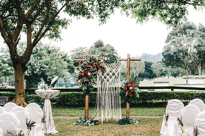 Đám cưới được tổ chức tại sân vườn với phông nền có hai gam màu chủ đạo là đỏ và nâu đất.