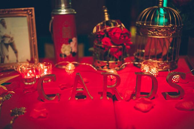 Sắc đỏ ngập tràn tại bàn tiếp tân trong hôn lễ từ khăn trải bàn, bông hoa đến khung chữ trang trí.