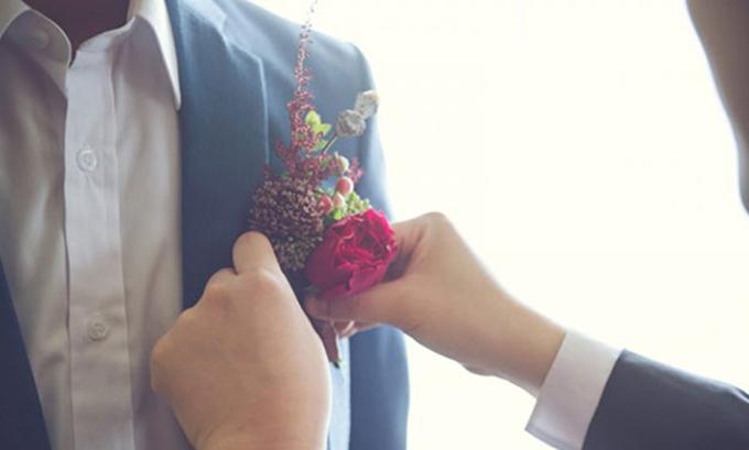 Chú rể lựa chọn hoa cài áo đỏ thẫm cùng tông với đôi giày mà cô dâu diện trong đám cưới.