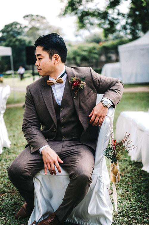 Chú rể tiếp tục sử dụng nơ màu nâu đất và hoa cài áo đỏ thẫm cùng tông với gam màu chủ đạo của đám cưới.