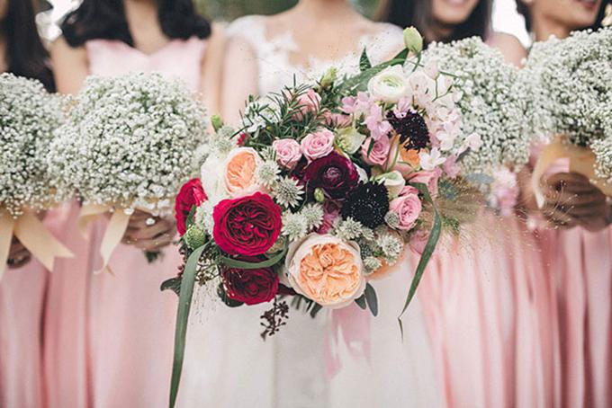 Hoa cầm tay của cô dâu được kết từ nhiều đóa hồng leo đỏ thẫm, hoa hồng và hoa lan tường. Cô dâu mang váy cưới màu trắng còn dàn phù dâu khoác lên mình chiếc váy hồng nhạt.