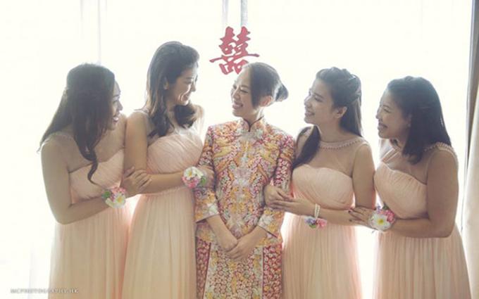 Dàn phù dâu diện bộ váy màu hồng đào đứng bên cô dâu với phục trang màu vàng đỏ.