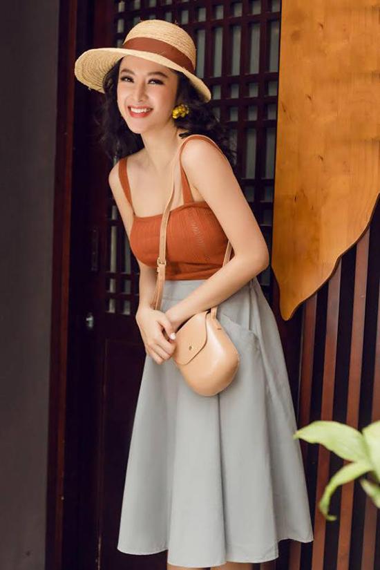 Phong cách hiện đại đan xen hơi thở cổ điển được thể hiện rõ nét trong cách phối áo hai dây tông nâu đi cùng chân váy xòe midi thanh lịch.