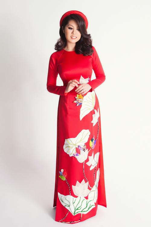 Chiếc áo dài của cô dâu với phom dáng truyền thống, tà dài chấm gót và đính họa tiết hoa sen được thực hiện thủ công. Dáng áo không cổphù hợp với khuôn mặt tròn của cô dâu.