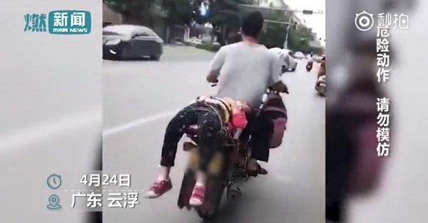 Người bố treo balô của con gái trước xe và trói con đằng sau xe để chở đến trường. Ảnh cắt từ video.
