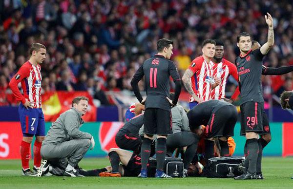 Laurent Koscielny bị trẹo chân ngay ở phút thứ 7 dù không va chạm với ai. Trung vệ 32 tuổi nằm xuống sân tỏ vẻ đau đớn. Griezmann cũng có mặt ở gần đó, lo lắng nhìn các bác sĩ chăm sóc vết thương cho sao Arsenal.