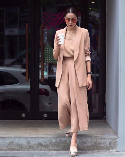 Hà Tăng diện bộ trang phục màu be nhã nhặn, chân đi giày bệt.