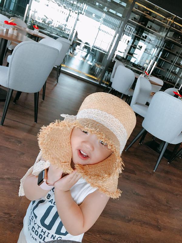 Nhóc tì hai tuổi làm điệu với chiếc mũ của mẹ khichụp ảnh.