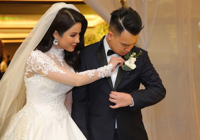 Diệp Lâm Anh ân cần chỉnh sửa hoa cài áo cho chồng.