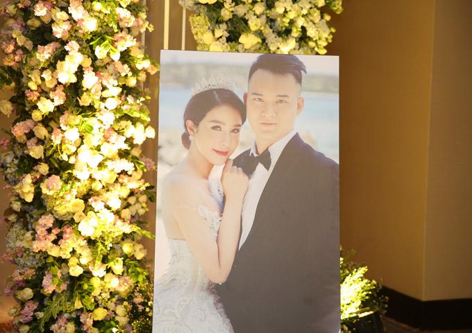 Ảnh cưới của hai vợ chồng phóng lớn trưng bên ngoài phòng tiệc.