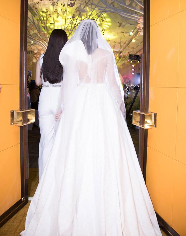 Cô dâu lộng lẫy trong bộ soiree gợi cảm, được bạn thân dắt vào trao cho chú rể.