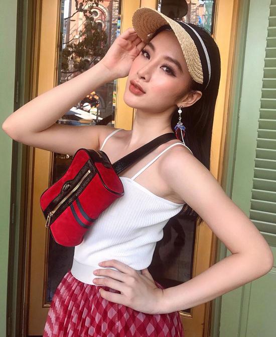 Xuống phố vào mùa nắng, Angela Phương Trinh chọn mũ cói chống nắng để phối cùng túi đeo ngực của Gucci, áo hai dây và chân váy kẻ ca rô.