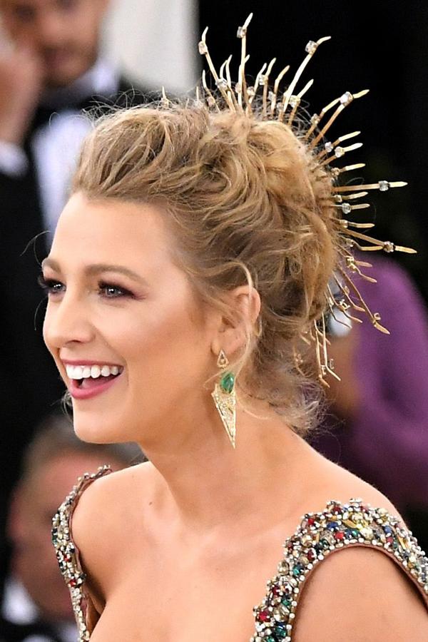 Blake Lively xuất hiện như một nàng công chúa với mái tóc bới cao gắn phụ kiện kim loại dài như vầng hào quang xung quanh tóc. Cô chọn lối trang điểm nhẹ nhàng mà tươi tắn với sắc hồng.
