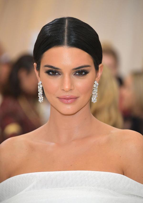 Kendall Jenner mang đến hình tượng cổ điển, quyến rũ với mái tóc đen bới thấp gọn gàng, mắt khói đen và son môi hồng nude phủ một chút bóng.