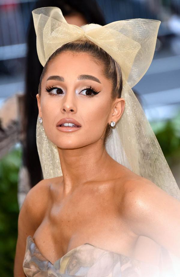Ariana Grande trung thành với kiểu tóc buộc đuôi ngựa cao quen thuộc nhưng làm mới bằng một chiếc nơ vàng to bản. Mắt khói đen trông sáng hơn nhờ sử dụng phấn tạo khối sáng có nhũ ở phía đầu mắt. Son bóng rất được ưa chuộng trên thảm đỏ Met Gala năm nay. Ariana sử dụng son bóng màu nude nâu pha chút nhũ ấn tượng.