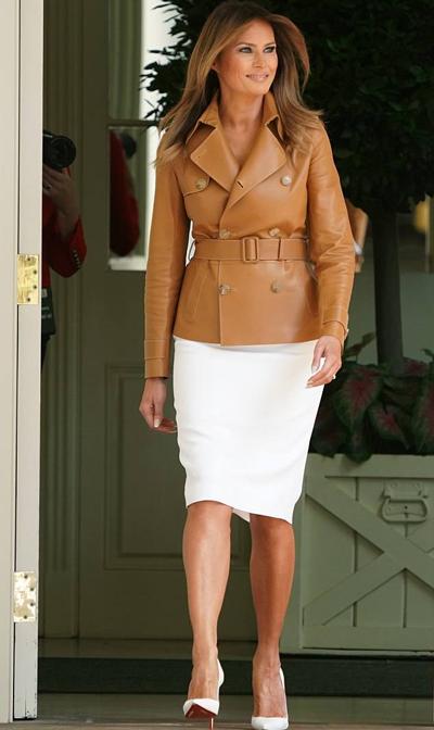 Giữa thời tiết khá oi bức, phu nhân tổng thống Mỹ vẫn mặc chiếc áo khoác da trị giá gần 6.000 USD của thương hiệu thời trang Ralph Lauren, kết hợp chân váy bút chì ôm sát màu trắng và đôi giày cao gót Christian Louboutin cùng màu.