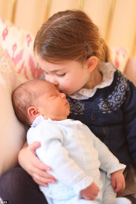 Công chúa Charlotte âu yếm hôn trán em trai mới sinh. Ảnh: PA.