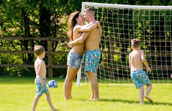 Đôi uyên ương ôm hôn nồng nàn cho dù có các con ở bên cạnh. Thương gia Michael ONeil mặc quần đùi ăn ý với các cậu nhóc con riêng của Danielle Lloyd.