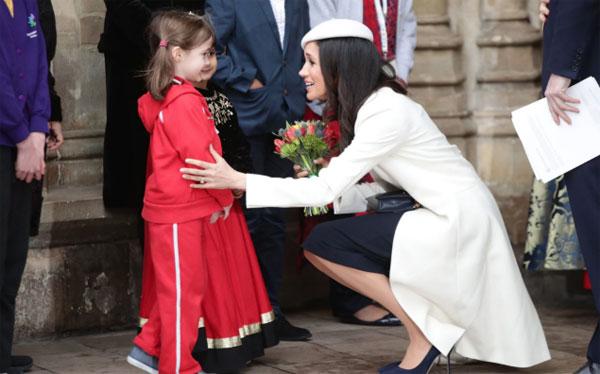 Meghan trò chuyện với một bé gái khi tham dự sự kiện tại Tu viện Westminster. Ảnh: PA.