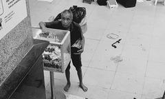 Cụ ông vô gia cư bỏ tiền vào thùng quyên góp ủng hộ người nghèo