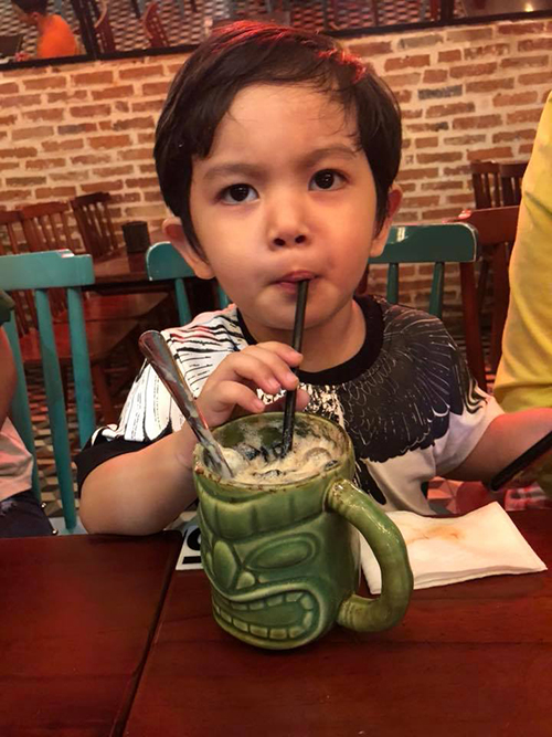 Kubi chăm chú uống nước khi theo mẹ ra quán cà phê.