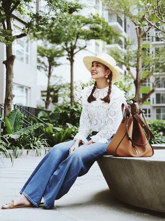 Siêu mẫu Thanh Hằng ăn mặc đúng điệu mùa hè với cách phối mũ nan kiểu gaucho đi cùng áo ren cổ điển, quần jean ống rộng, dép đế bệt quai da.