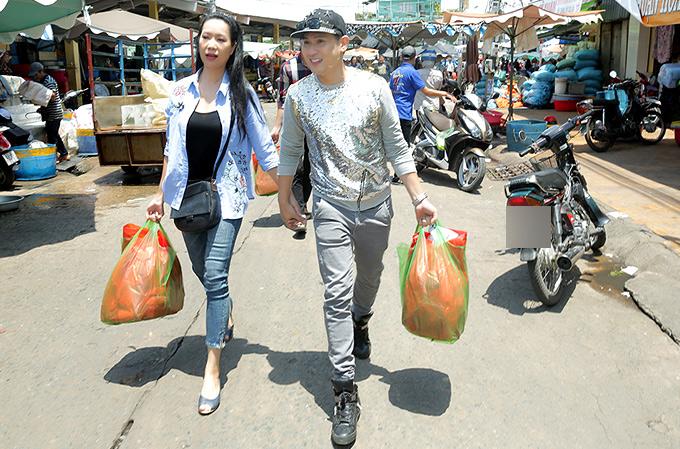 Ca sĩ Nguyên Vũ tình cảm nắm tay, dắt Trịnh Kim Chi đi chợ mua các nhu yếu phẩm như bánh kẹo, mì gói, sữa, dầu ăn... tặng bà con nghèo.